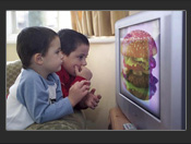 Two children watching television advert